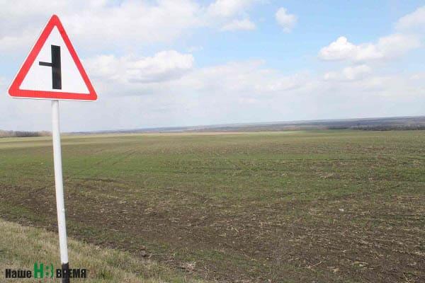 На этом поле в Мясниковском районе планируют построить МЭОК. За полем – тузловские склоны и речка.